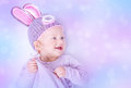 Cute easter bunny portrait of happy baby girl wearing knitted hat with rabbit ears on purple blur background beautiful Royalty Free Stock Photo