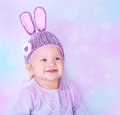 Cute easter bunny portrait of happy baby girl wearing knitted hat with rabbit ears on purple blur background beautiful Stock Images