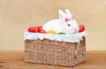 Cute easter bunny sitting in basket with colorful eggs on golden background Stock Image