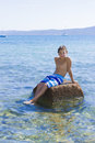 Cute eleven years old boy sitting on a rock in the sea Stock Photography