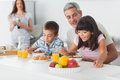 Cute family eating breakfast in kitchen together Royalty Free Stock Photo