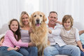 Cute family relaxing together on the couch with their dog Royalty Free Stock Photo