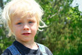 Cute farm kid close up of blonde toddler boy outside in the summer Royalty Free Stock Photos