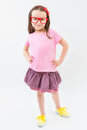 Cute fashion-monger girl in pink dress tshirt and skirt red glasses frames. Royalty Free Stock Photo