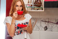 Cute female with freckles drinking coffee from cup in kitchen Royalty Free Stock Image