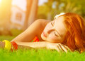 Cute female on green grass redhead lying down fresh with closed eyes sleeping outdoors enjoying day spa luxury resort warm sun Royalty Free Stock Image