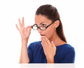 Cute female looking embarrassed with hand on mouth shy girl over glasses in white background copyspace Stock Images