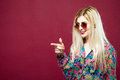 Cute Female Model with Sunglasses and Long Hair Wearing Colorful Shirt on Pink Background. Amazing Blonde is Posing in Royalty Free Stock Photo