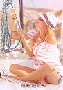 Cute female working on sailboat sitting the deck of pulling rope water transport beautiful model posing for luxury photo shoot Stock Photos