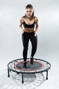 Cute fitness-girl make exercise on rebounder Royalty Free Stock Photo
