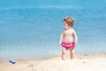 Cute funny baby girl with curly hair in sand on beach playing a Royalty Free Stock Photography
