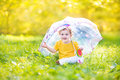 Cute funny baby girl playing in rain under umbrella Royalty Free Stock Photo