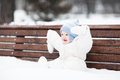 Cute funny baby sitting on a bench in a park Royalty Free Stock Photo