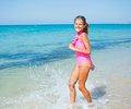 Cute girl on the beach beautiful happy smiling runs along Royalty Free Stock Images
