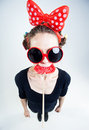Cute girl with a big red lollipop and funny sunglasses studio shot Stock Photography