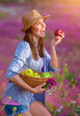 Cute girl biting red apple young farmer enjoying harvest relaxation in beautiful floral garden eating fruits healthy lifestyle Stock Images