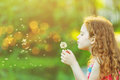Cute girl blowing dandelion in spring park. Royalty Free Stock Photo