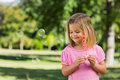 Cute girl blowing soap bubbles at park young the Royalty Free Stock Images