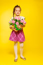 Cute girl with braid hold pail and pink tulips small beautiful holding on the yellow background Stock Photos