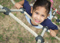 A cute girl is climbing on the rope ladder at public playground Royalty Free Stock Images