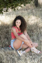Cute girl with curly hairs sitting on the dry grass Royalty Free Stock Photo