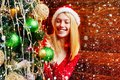 Cute girl is decorating the Christmas tree indoors. Christmas decorations. Fashion portrait of model girl indoors with Royalty Free Stock Photo