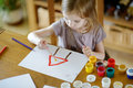 Cute girl is drawing with paints in preschool