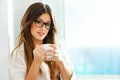 Cute girl drinking coffee at window. Royalty Free Stock Photo