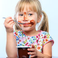 Cute girl eating chocolate yogurt. Royalty Free Stock Photo