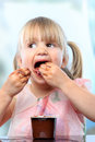 Cute girl eating chocolate yogurt with hands. Royalty Free Stock Photo