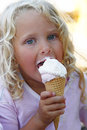 Cute girl enjoying ice cream child with blond curly hair in summer eat an cone vanilla and strawberry Stock Photography