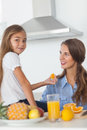 Cute girl giving an orange segment to her mother in the kitchen Royalty Free Stock Photography