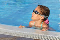 Cute girl in goggles swimming in pool smiling Royalty Free Stock Photography