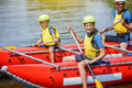 Cute girl in helmet and live vest with paddle ready for rafting on the catamaran Royalty Free Stock Photo