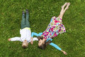 Cute girl with her little brother lying on the green grass Royalty Free Stock Photo