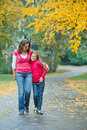 Cute girl with her mother walking in park Stock Photos