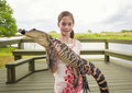 Cute girl holding a crocodile near florida everglades