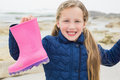 Cute girl holding her wellington boot at beach portrait of a smiling young the Royalty Free Stock Images