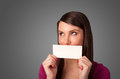 Cute girl holding white card at front of her lips with copy spac space on gradient background Royalty Free Stock Images