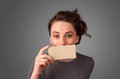 Cute girl holding white card at front of her lips with copy spac space on gradient background Royalty Free Stock Photo