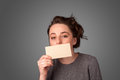 Cute girl holding white card at front of her lips with copy spac space on gradient background Royalty Free Stock Photos