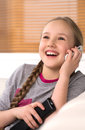 Cute girl at home cheerful little talking on the mobile phone Stock Photography