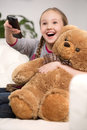 Cute girl at home cheerful little watching tv and holding toy bear Stock Photos