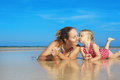 Cute girl kissing happy smiling mother on sea beach Royalty Free Stock Photo