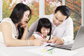Cute girl learn to write with parents at home photo of attractive little try on the book her shot autumn background on the window Royalty Free Stock Photos