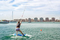 Cute girl learns to surf on background of yachts in Marina Royalty Free Stock Photo