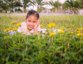 A cute girl lie down on a field behind yellow flowers Stock Photography