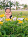 A cute girl lie down on a field behind yellow flowers Royalty Free Stock Image