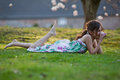 Cute girl lies dreamy in the grass Royalty Free Stock Photo