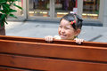 Cute girl little hiding behind the wooden bench Stock Photo